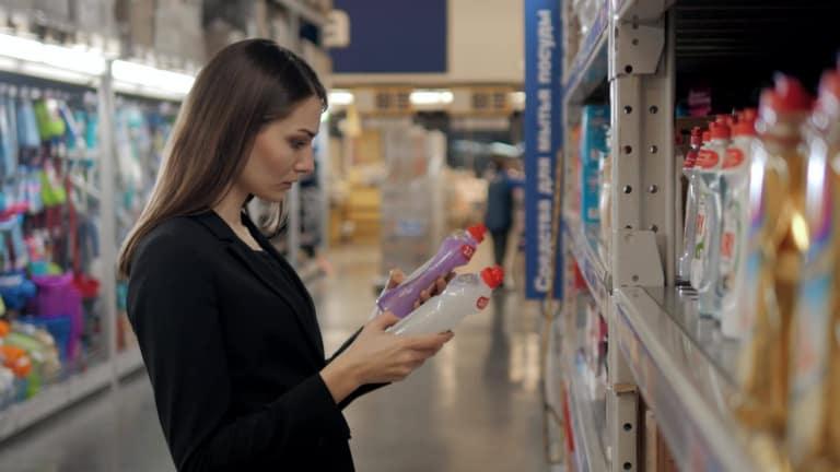 femme choisissant entre deux produits éco labellisés, comparant les prix