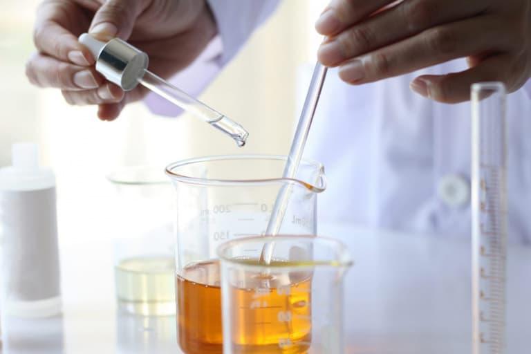 chimiste en train de prélever une substance pour fabriquer des cosmétiques